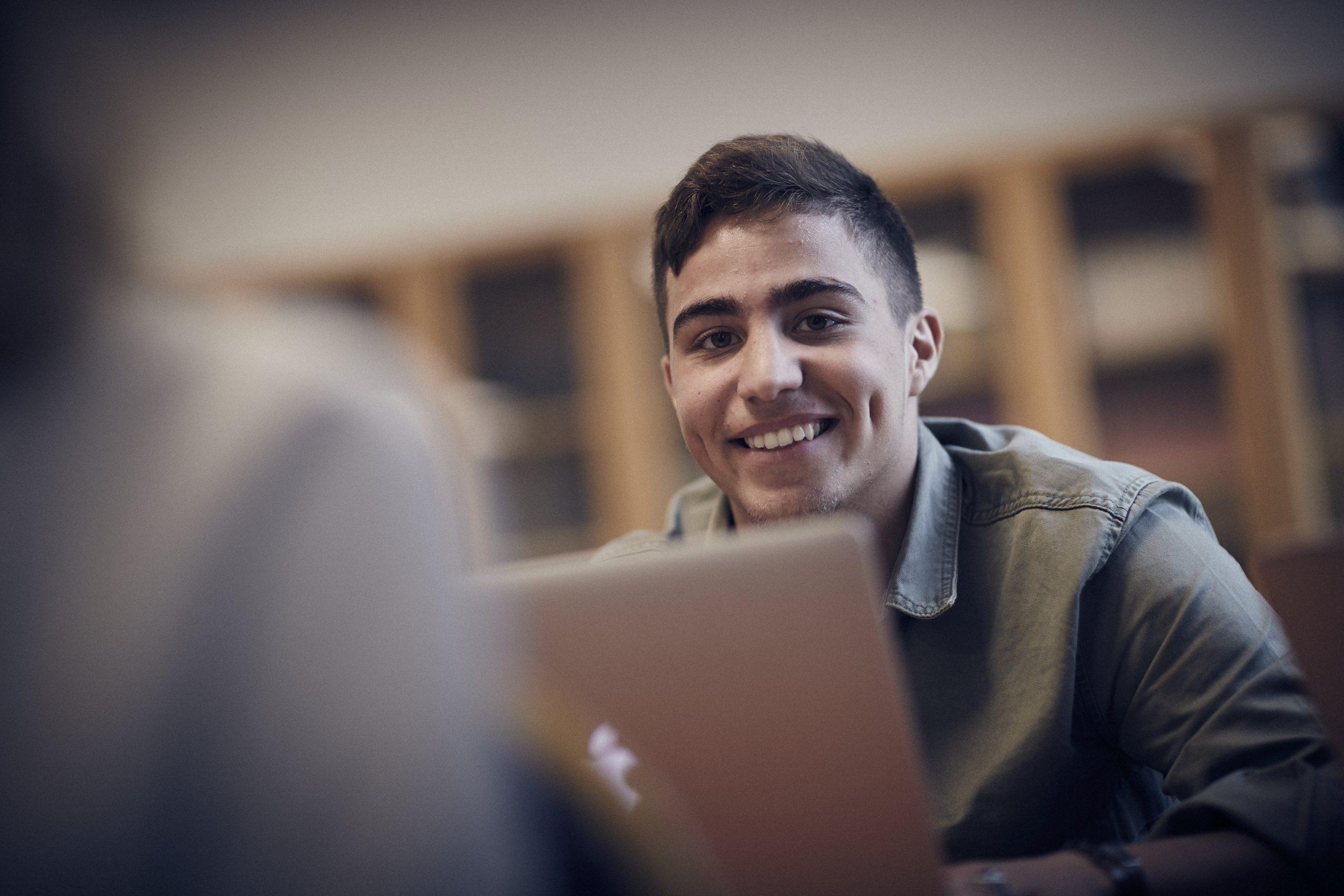 Adam, elev ler framför kameran. Han har på sig en grön skjorta
